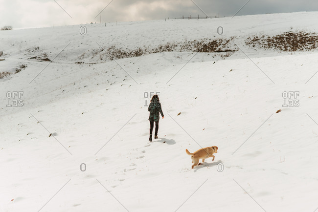 Young woman and a yellow lab walking up a snowy hillside