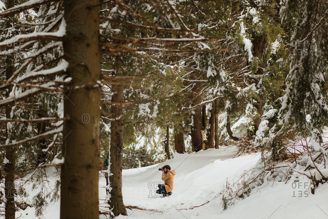Photographer taking a photo in a snowy forest