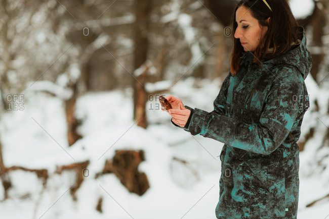 Woman holding a pine cone in a snowy forest