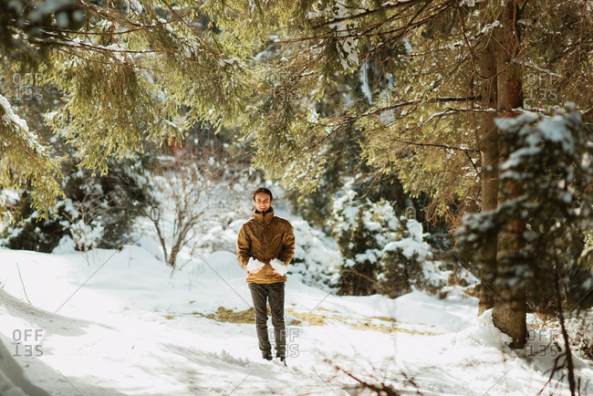 Young man holding large chunks of snow in a forest