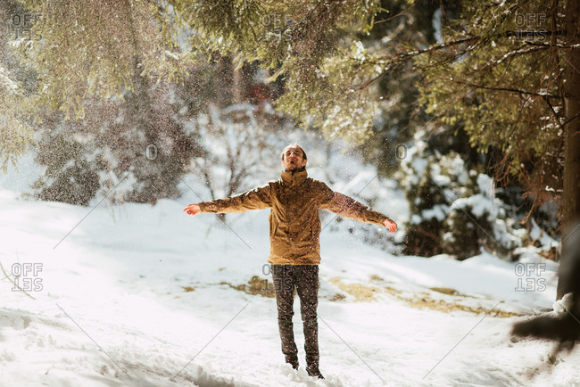 Man enjoying a spray of snow in the forest