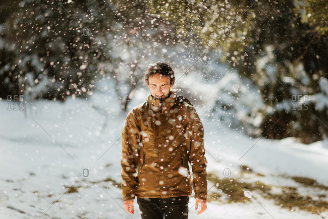 Young man standing under scattering snow from a tree branch