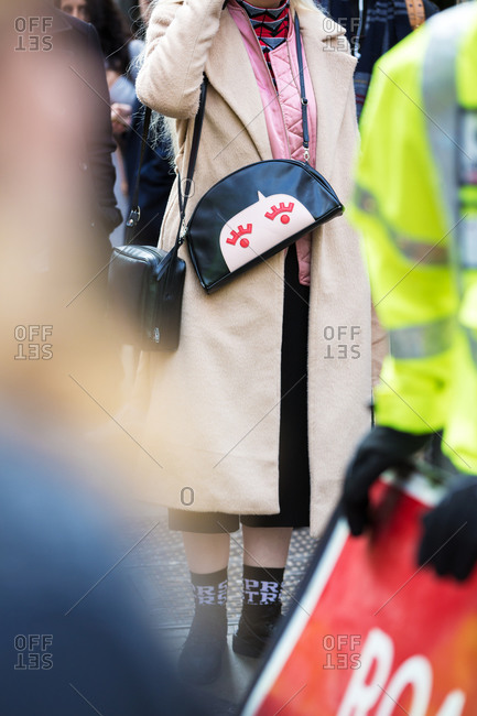 Woman carrying a purse with a face