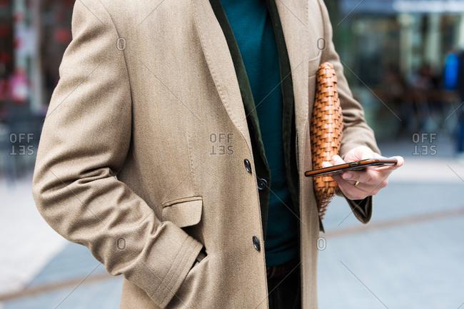 Man in tan coat using cell phone