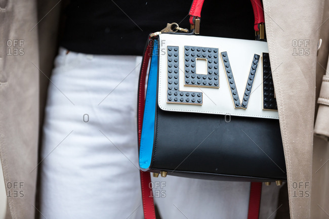 "Close up of a purse that says ""Love"" with toy bricks"