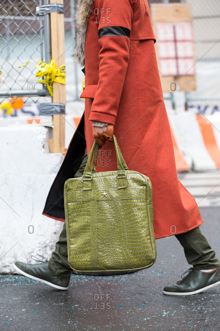 Person wearing red jacket and carrying green alligator skin bag