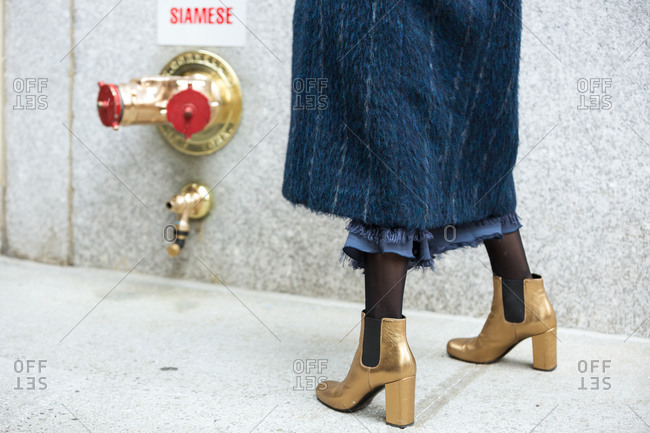 Woman wearing gold heeled shoes and blue furry coat