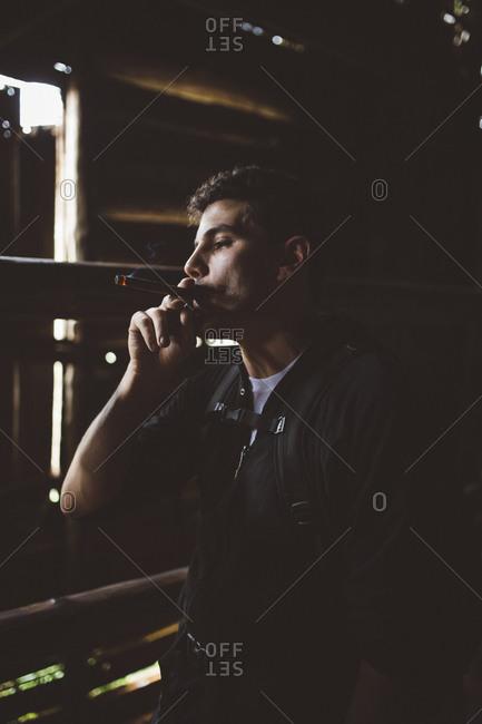 Man smoking cigar in barn