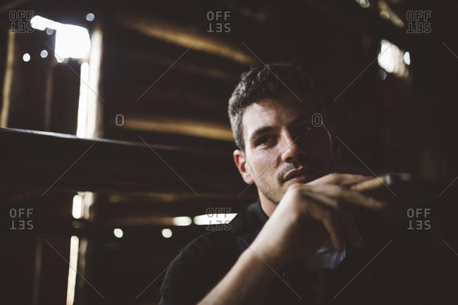 Man smoking cigar in a barn