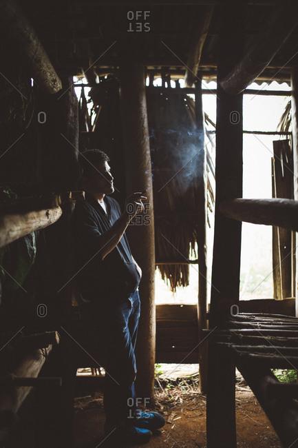 Man smoking cigar in shed