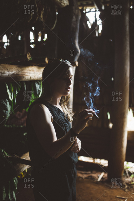 Cuba - January 12, 2016: Woman with cigar in tobacco shed