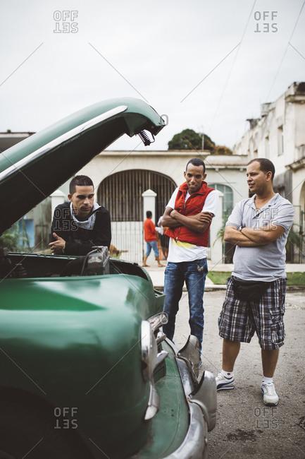 January 13, 2016: Men looking at car on Cuban street