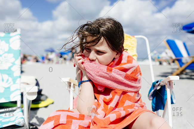Girl sitting on a beach chair wrapped in a towel