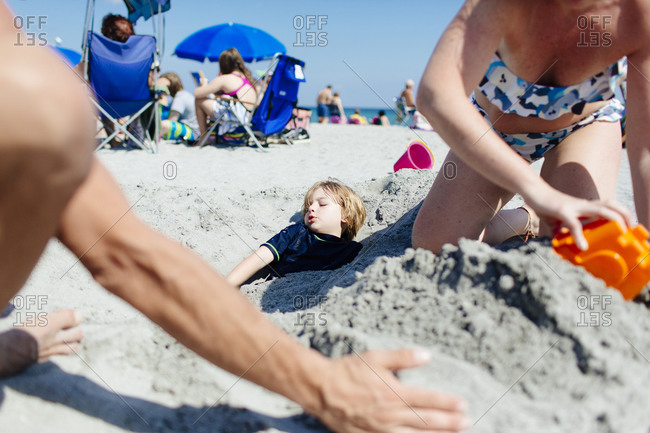 Man and woman burying their son in the sand at the beach