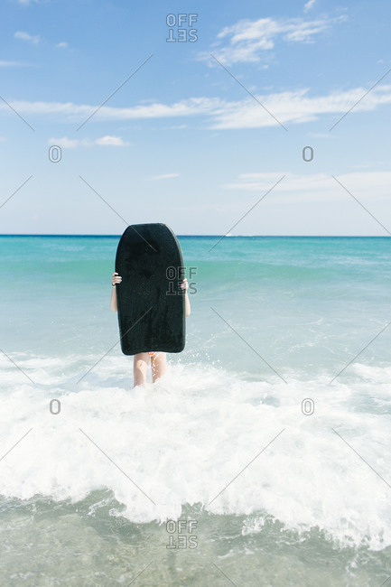 Girl standing in the surf at the beach holding a body board