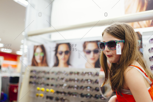 Tween girl trying on sunglasses in a store
