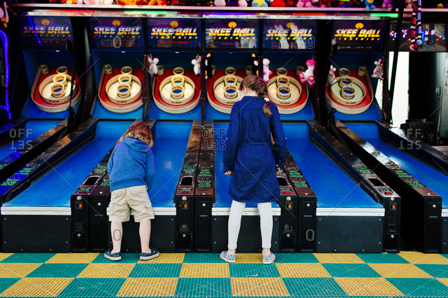 Boy and girl playing skeeball together in an outdoor arcade