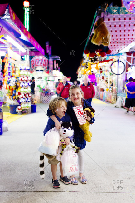 Boy and girl standing together at a fairground