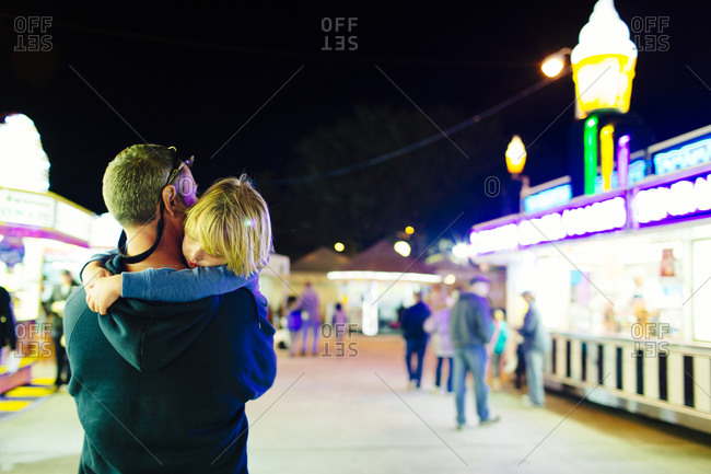 Man carrying his son through a fairground at the end of the day
