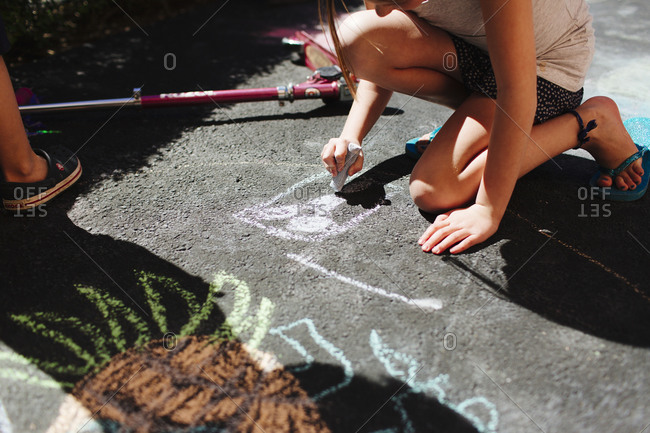 Girl drawing on a sidewalk with color chalk