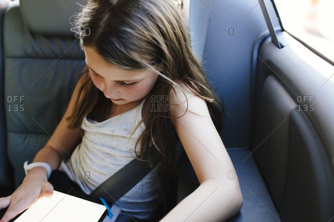Girl using digital tablet in the backseat of a car