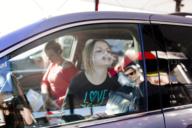 Girl pressing her face against the window of her car and making silly faces