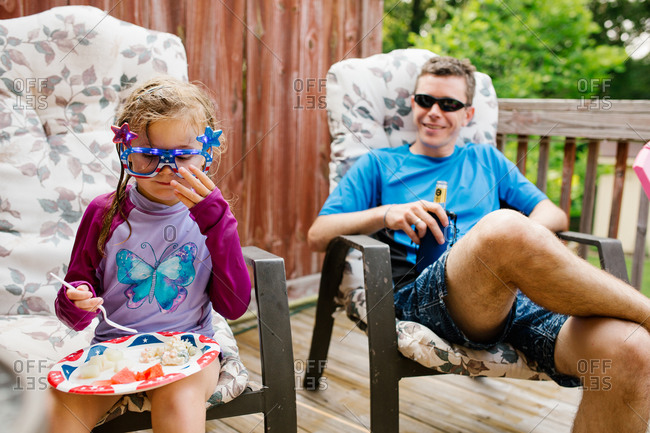 Little girl and her father sitting on a deck at a Fourth of July party