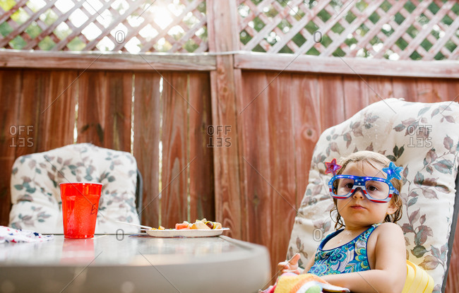 Little girl sitting at a table eating at a Fourth of July party