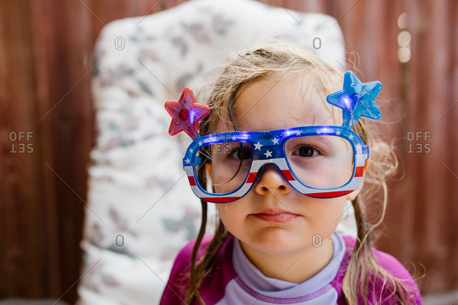 Little girl wearing Fourth of July light-up glasses