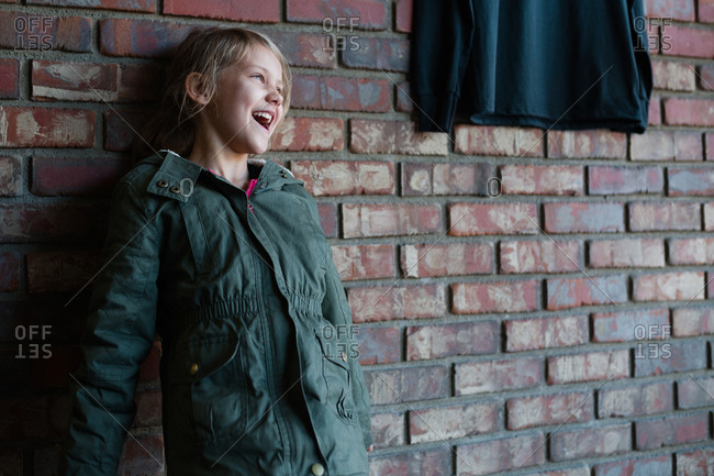 Young girl standing against a brick wall laughing