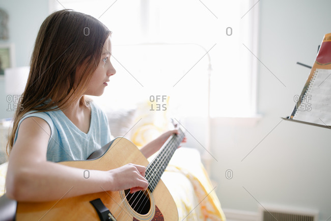 Young girl playing guitar in her room