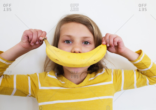 Young girl covering her mouth with a banana