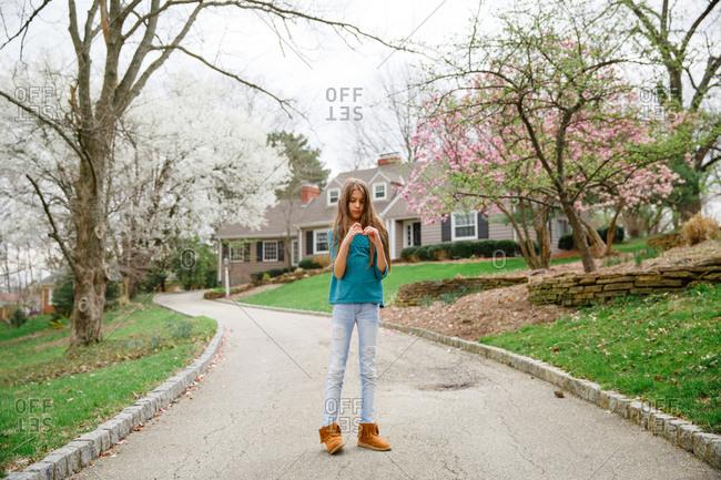 Tween girl standing on her driveway