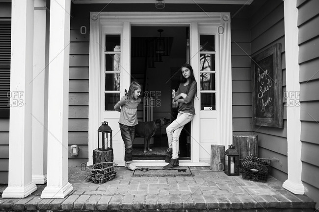 Two girls standing on their front porch