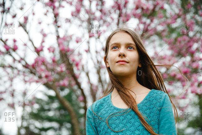 Tween girl standing in front of a blooming magnolia tree