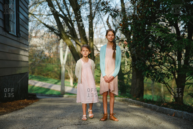 Portrait of two girls standing outside wearing Easter dresses