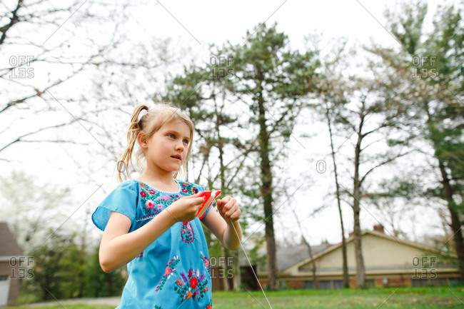 Young girl flying a kite in her yard