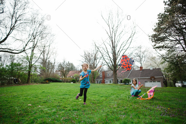 Young girls flying a kite in their yard
