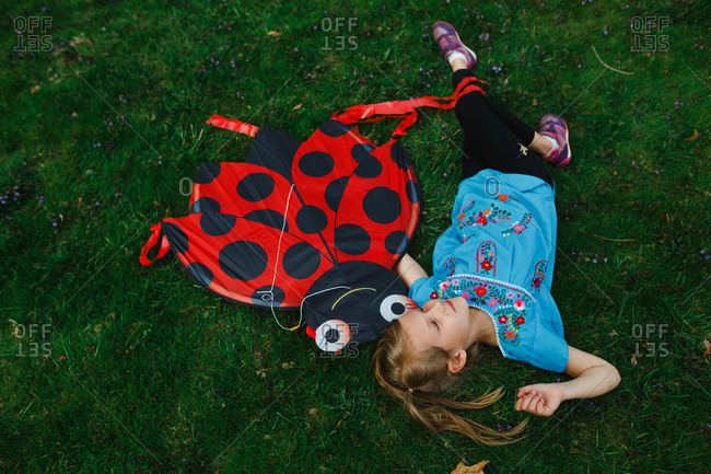 Young girl lying down in the grass with her kite