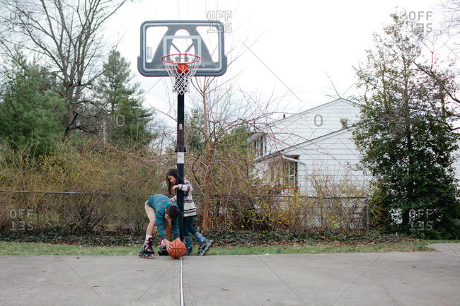 Brother and sister playing basketball while rollerblading