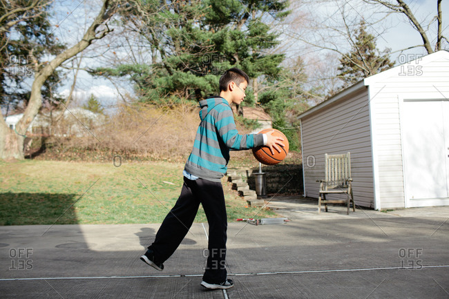Boy dribbling a basketball on a court at a neighborhood park