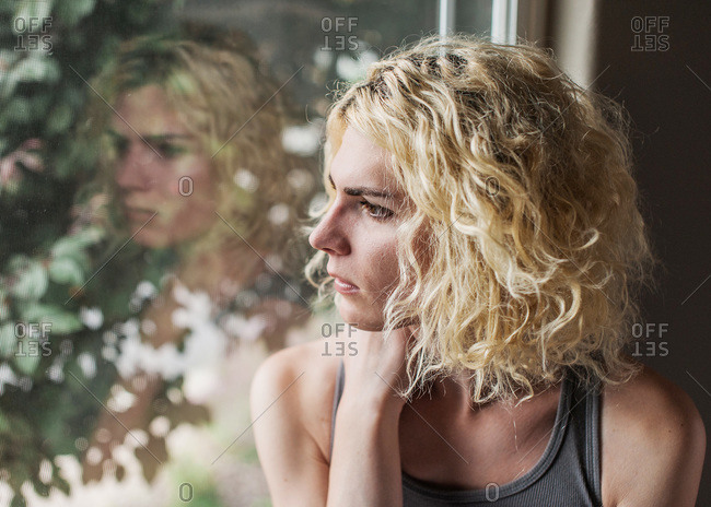 Blonde woman sitting next to a window