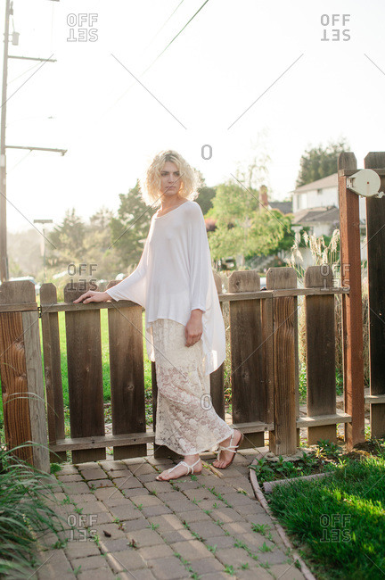 Blonde woman standing at a wooden gate