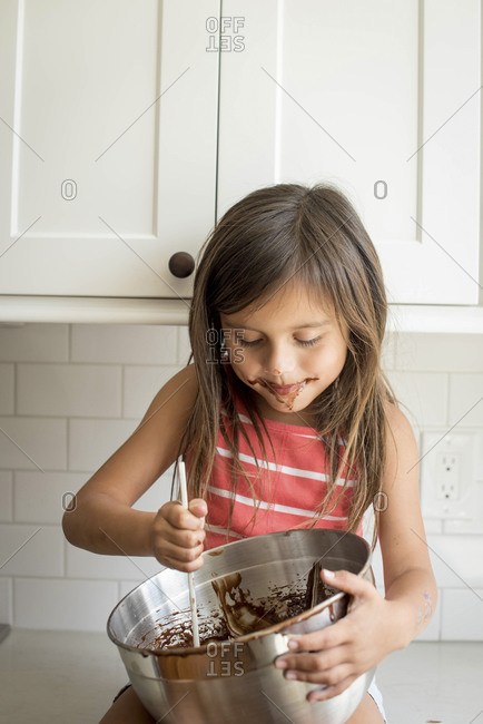 Young girl eating chocolate batter from mixing bowl