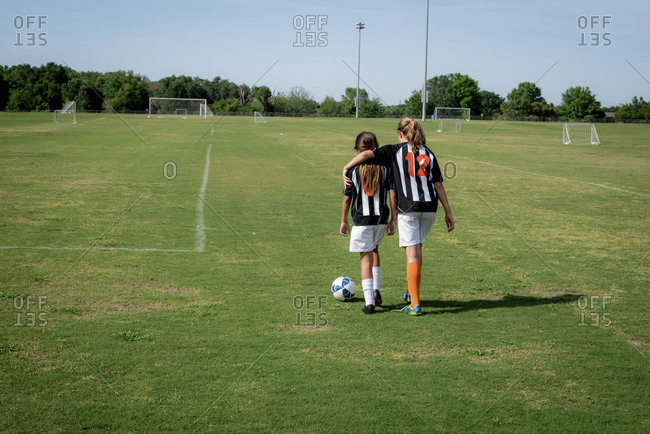 Girl with arm around teammate on soccer field