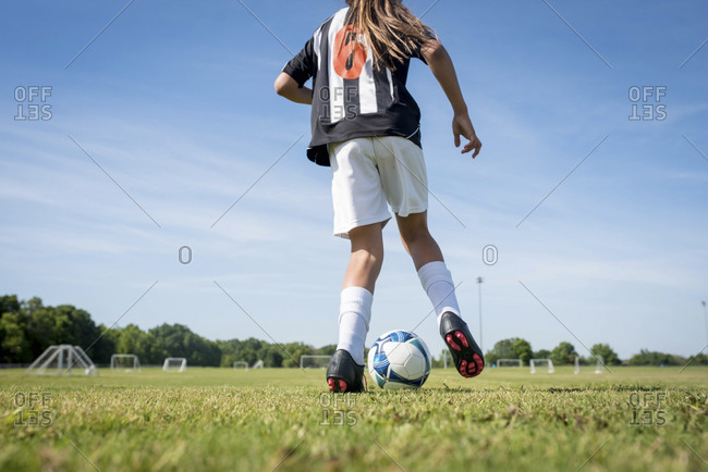 Young girl dribbling soccer ball on field