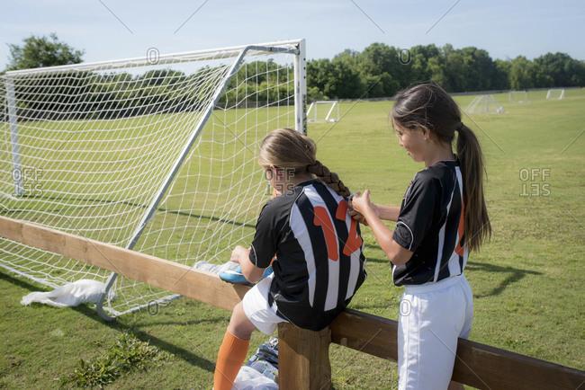 Girl braids her teammate's hair before soccer match