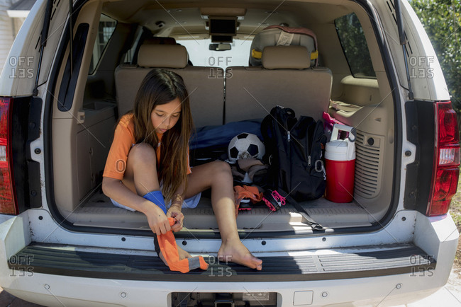 Young soccer player puts on her shin guards in the back of car