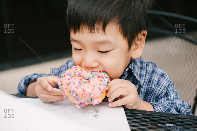 Young boy eating a donut with icing and sprinkles