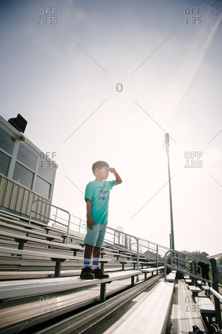 Boy standing on bleachers at stadium